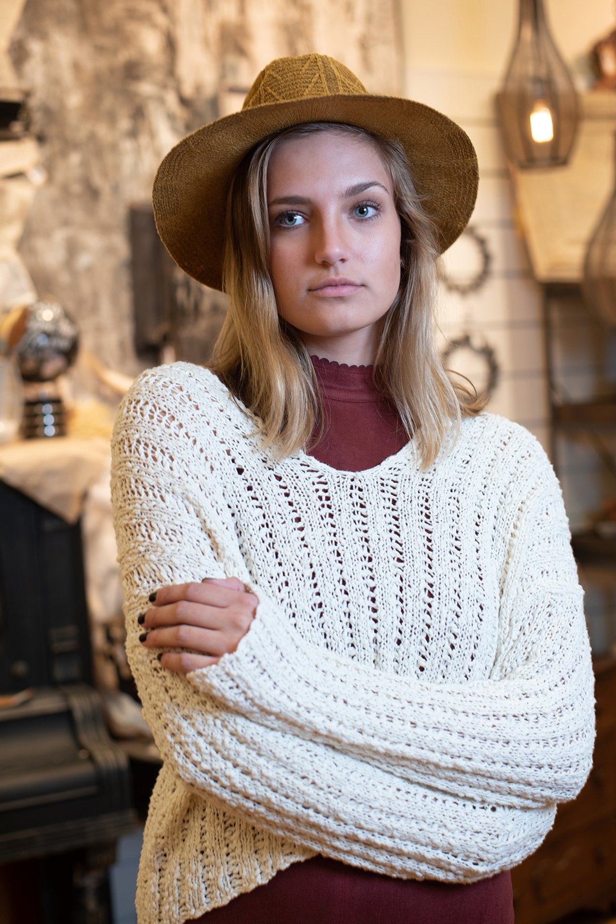 girl wearing white sweater and brown hat