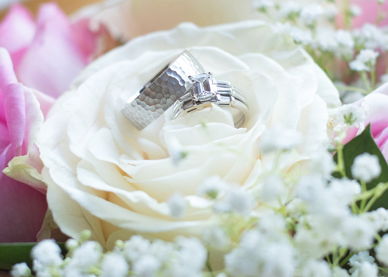wedding rings sitting on top of wedding bouquet