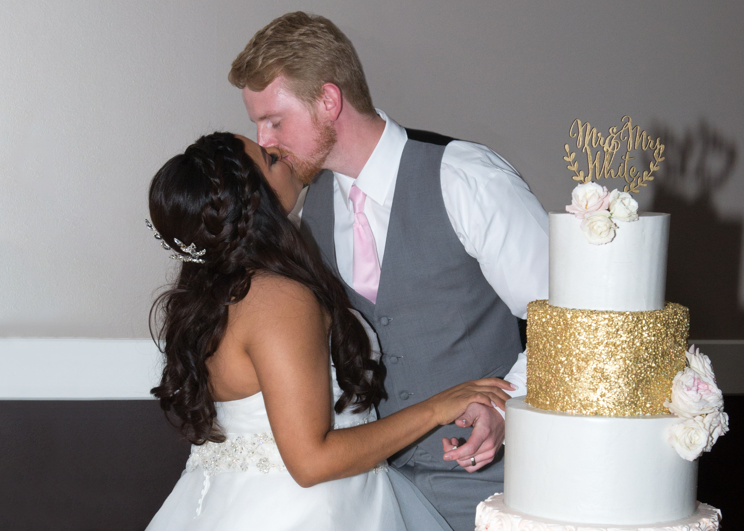 bride and groom kissing after cutting the cake