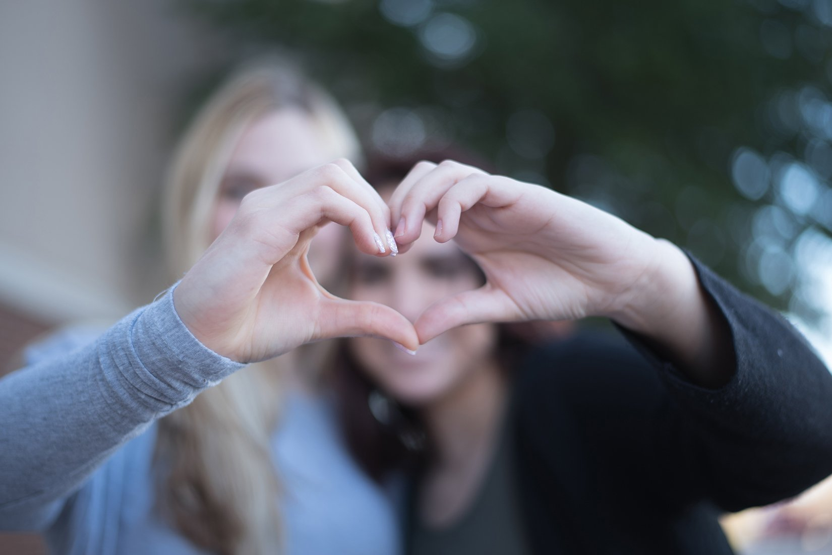 girls holding hands in shape of a heart