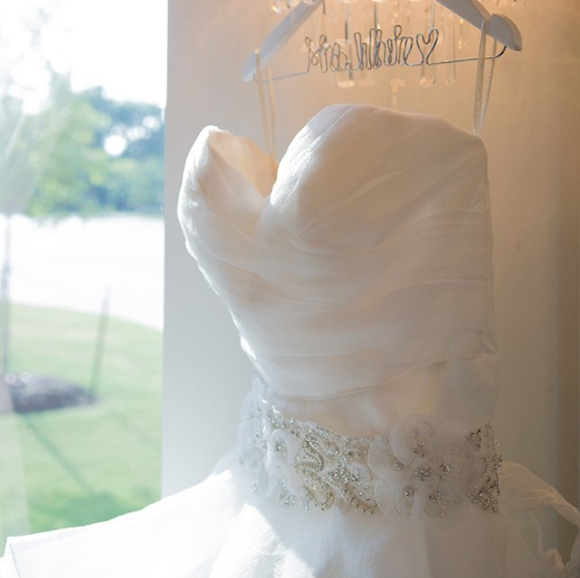 white wedding dress hanging near a window