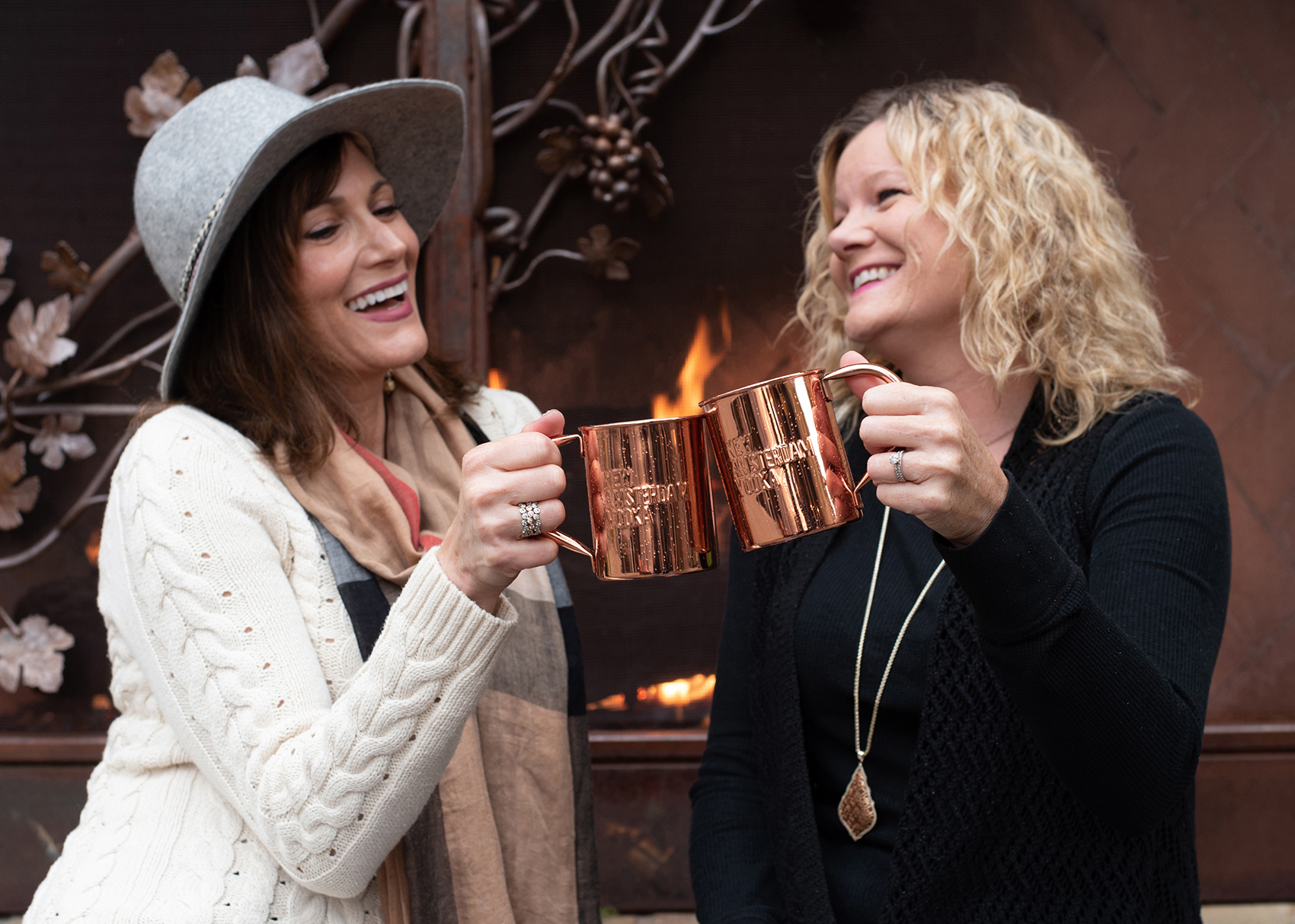 friends toasting in front of a fireplace at watters creek